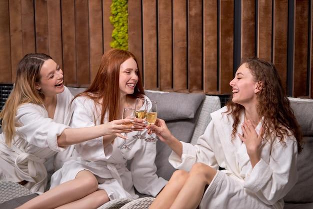 Ontspannen dames genieten van het drinken van champagne in de spa drie mooie vrouwen die badjassen dragen met een koele rustvakantie