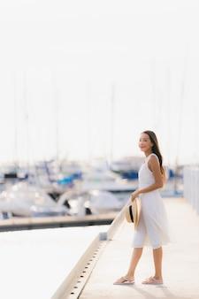 Ontspannen de gelukkige jonge aziatische vrouw van de vrouwenvrije tijd ontspant rond jachthaven