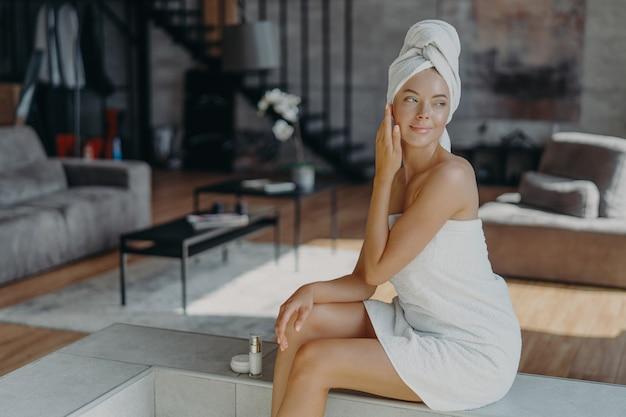 Ontspannen doordachte vrouw gewikkeld in badhanddoek, geldt anti-rimpel crème of bodylotion, vormt in de woonkamer thuis, ziet er peinzend goed uit