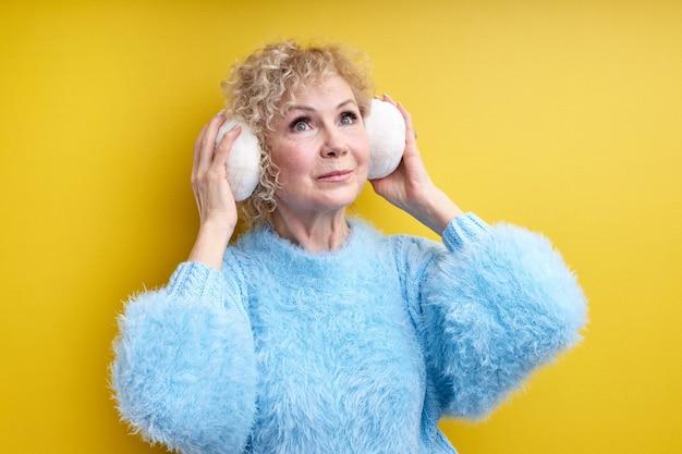 Ontspannen elegante senior vrouw luisteren naar muziek in koptelefoon, geïsoleerde, oudere vrouw met grijs haar poseren, met witte grote headset, verrast door moderne muziek