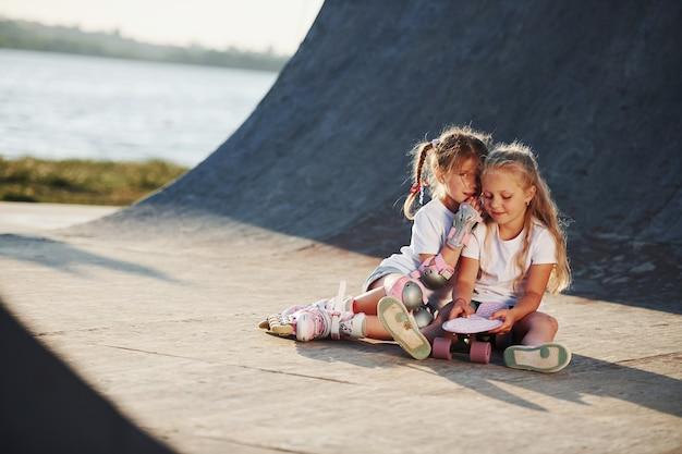 Ontspannen en een gesprek voeren. op de helling voor extreme sporten. twee kleine meisjes met rolschaatsen buiten hebben plezier.