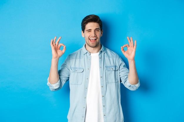 Ontspannen en zelfverzekerde man die ok tekens toont en knipoogt, alles oke gebaar, staande tegen een blauwe achtergrond.