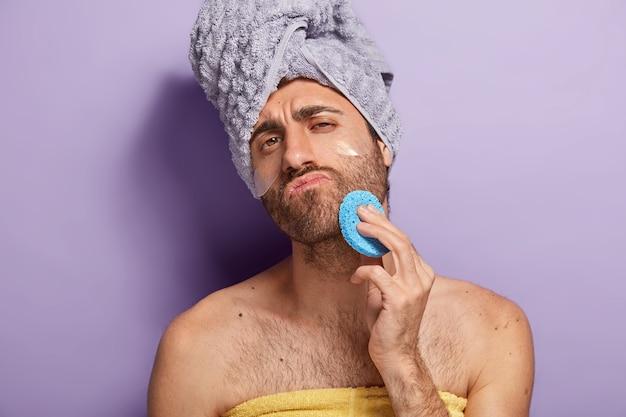Ontspannen ernstige man met stoppels veegt huid op gezicht na het douchen, houdt cosmetische spons, gewikkeld in een zachte handdoek