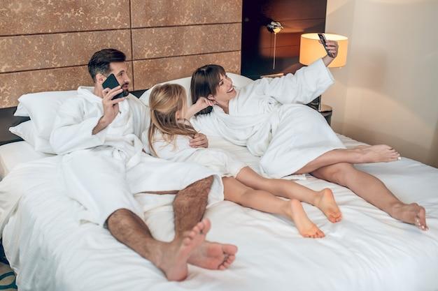 Ontspannen familie in witte gewaden liggend in bed en ziet er ontspannen uit