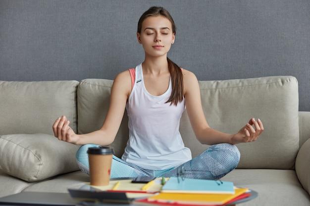 Ontspannen geconcentreerde tiener gekleed in vrijetijdskleding, zit in yogapositie, mediteert en heeft pauze na hard werken, drinkt afhaalkoffie