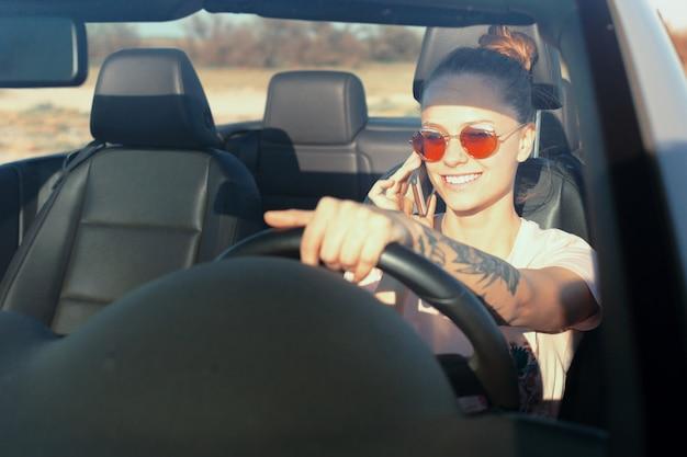 Ontspannen gelukkige vrouw die in een auto reist