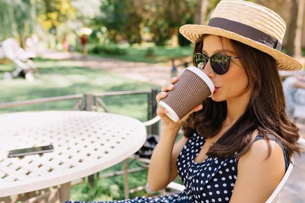 Ontspannen gelukkige vrouw in zonnebril en strooien hoed buiten koffie drinken