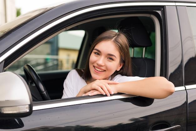 Ontspannen gelukkige vrouw op zomer roadtrip reizen vakantie leunend uit autoraam op blauwe hemel muur.