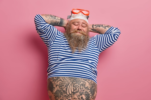 Ontspannen getatoeëerde mannelijke zwemmer houdt de handen achter het hoofd, sluit de ogen, draagt een zwembril en een pet, heeft een grote buik die uitsteekt uit een ondermaats zeemansshirt geïsoleerd op een roze muur. zomervakantie