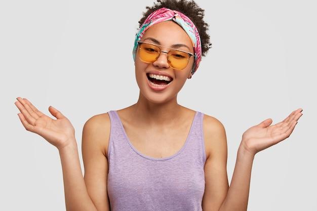 Ontspannen grappige donkere huid jonge vrouw glimlacht en spreidt handen