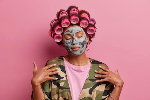 Ontspannen huisvrouw met haarkrulspelden en schoonheidsmasker, sluit de ogen, gekleed in een ongedwongen huiselijk gewaad, geniet van vrije tijd voor zichzelf, geïsoleerd op roze. mensen, wellness en beauty concept
