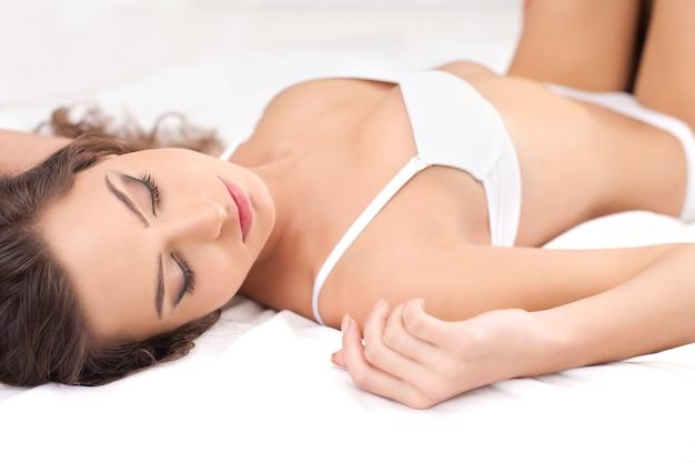 Ontspannen in bed. mooie jonge vrouw in lingerie die in bed ligt en ogen gesloten houdt