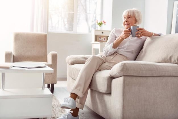 Ontspannen in de ochtend. mooie oudere vrouw zittend op de bank in haar woonkamer, koffie drinken en iets overweegt