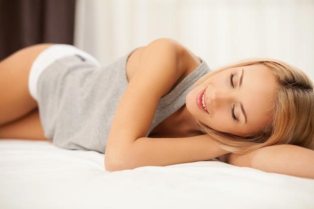 Ontspannen in de slaapkamer. glimlachende jonge blonde haarvrouw in hemd en slipje die op bed liggen en ogen gesloten houden
