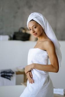 Ontspannen jong kaukasisch vrouwelijk model in witte handdoek, voelt zich verfrist na het nemen van een douche, heeft een gezonde schone zachte huid, vormt in een gezellige badkamer. concept voor vrouwen, schoonheid en hygiëne.