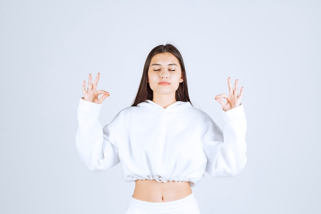 Ontspannen jong meisjesmodel dat gekruiste vingers met gesloten ogen toont.