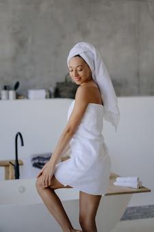 Ontspannen jong vrouwelijk model in witte handdoek, voelt zich verfrist na het douchen