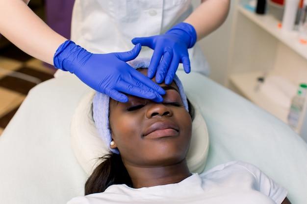 Ontspannen jonge afrikaanse vrouw die voorhoofdmassage in kuuroord ontvangt. vrouwenmassagist in blauwe rubberen handschoenen die gezichtsmassage uitvoeren. spa, massage concept