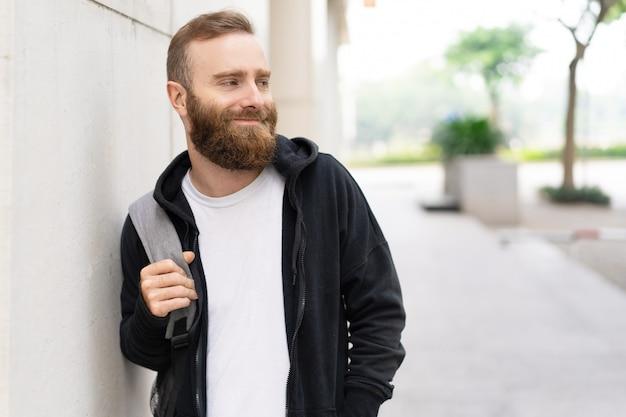 Ontspannen jonge bebaarde man lopen op straat