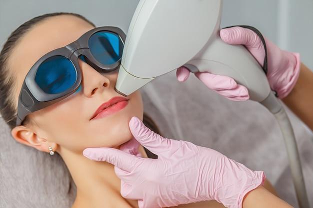 Ontspannen jonge cliënt die laserepilation van de haarverwijdering ontvangt. close-up zijaanzicht