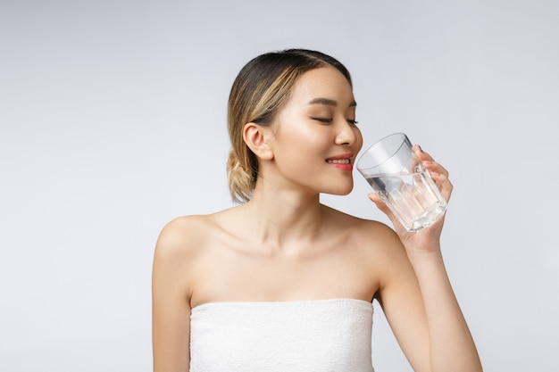Ontspannen jonge glimlachende vrouw die schoon water drinkt.