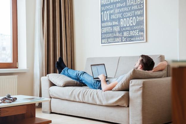 Ontspannen jonge man liggend op de bank en met behulp van laptop thuis