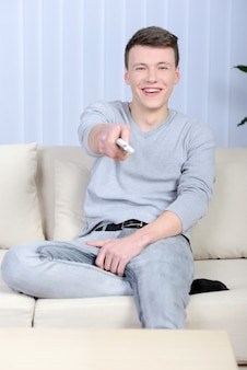 Ontspannen jonge man tv kijken thuis in lichte woonkamer