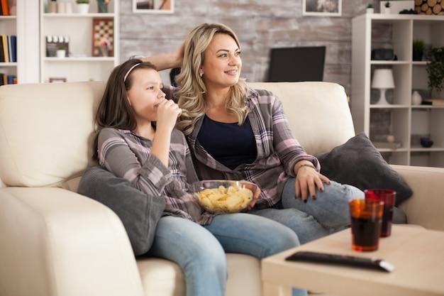 Ontspannen jonge moeder en vrolijke dochter tv-kijken zittend op de bank chips eten.