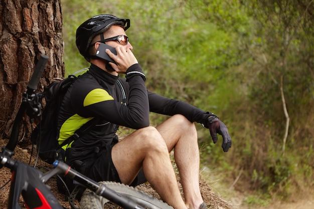 Ontspannen jonge ruiter die sportkleding en beschermende uitrusting draagt, die telefoongesprek heeft tijdens kleine pauze terwijl het fietsen op hulpfiets in stadspark. mensen, technologie en actieve levensstijl
