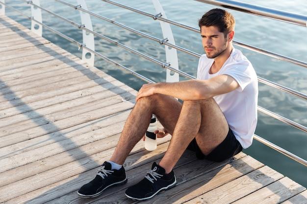 Ontspannen jonge sportman met fles water zittend en ontspannend op de pier