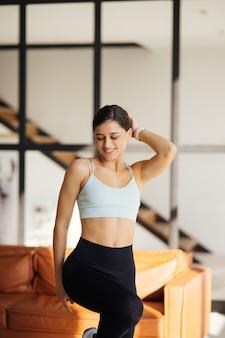 Ontspannen jonge sportvrouw gekleed in activewear poseren