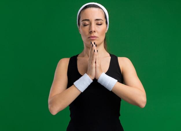 Ontspannen jonge, vrij sportieve vrouw met hoofdband en polsbandjes die de handen bij elkaar houden met gesloten ogen