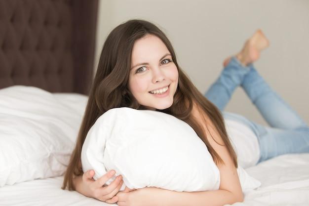 Ontspannen jonge vrouw die in bed op maag ligt