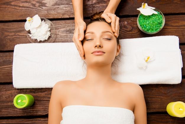 Ontspannen jonge vrouw die in kuuroordsalon met gesloten ogen legt en massage heeft