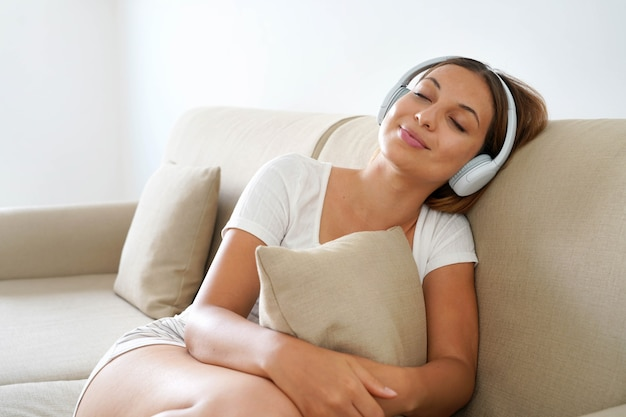 Ontspannen jonge vrouw in koptelefoon luisteren naar muziek terwijl ze een kussen knuffelt dat thuis op de bank slaapt