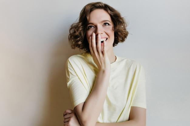 Ontspannen jonge vrouw in t-shirt genieten van fotoshoot op lichte muur. zalig meisje met kort kapsel positieve emoties uitdrukken.