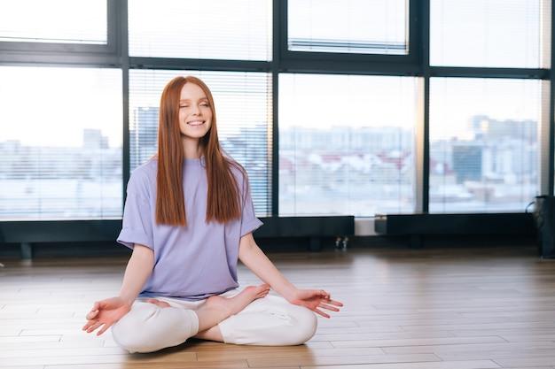 Ontspannen jonge vrouw mediteren zittend op de vloer in lotus houding op de achtergrond van het raam in de kantoorruimte
