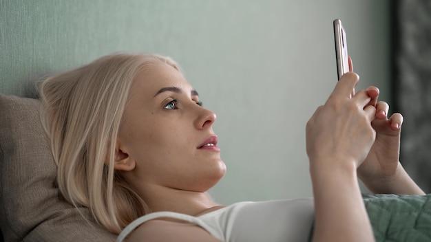 Ontspannen jonge vrouw met behulp van slimme telefoon surfen op sociale media, nieuws controleren, mobiele games spelen of sms'en zittend op de bank.