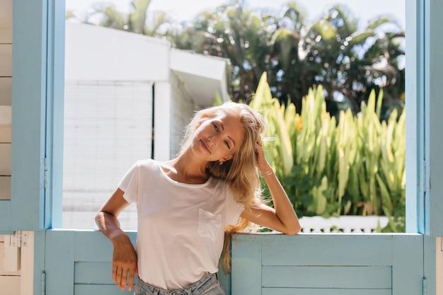 Ontspannen jonge vrouw met een gebruinde huid die zich dichtbij venster bevindt. aantrekkelijk europees meisje met lang glanzend haar lachend in de ochtend.