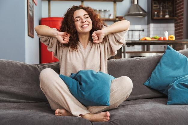 Ontspannen jonge vrouw met huiskleren glimlachend en zittend op de bank in appartement