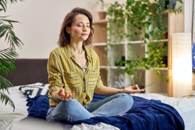 Ontspannen jonge vrouw zittend op bed in lotushouding thuis mediteren