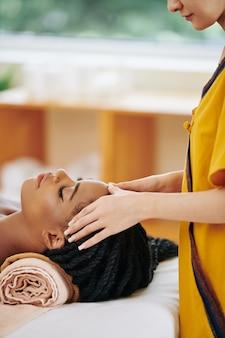Ontspannen jonge zwarte vrouw die van hoofdmassage in kuuroordsalon geniet