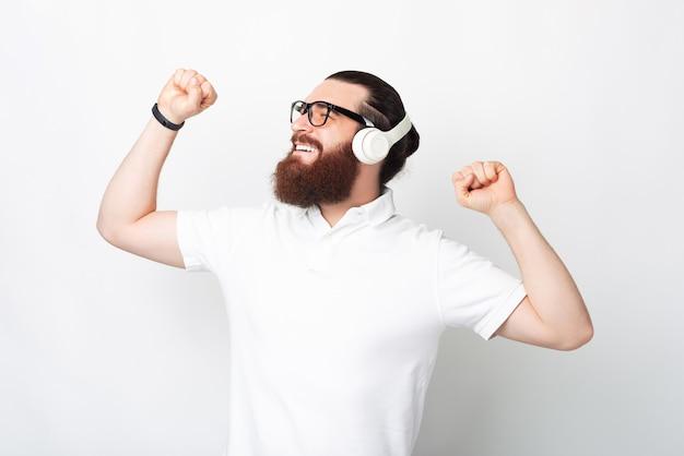 Ontspannen jongeman danst terwijl hij via een koptelefoon naar de muziek luistert.