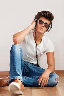 Ontspannen jongeman luisteren naar muziek op de hoofdtelefoon