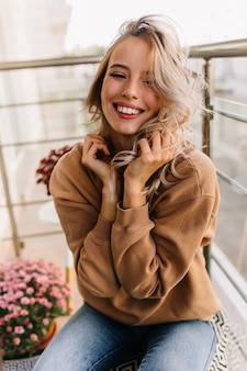 Ontspannen kaukasisch meisje zit op balkon in de ochtend. fascinerende jonge vrouw die lacht