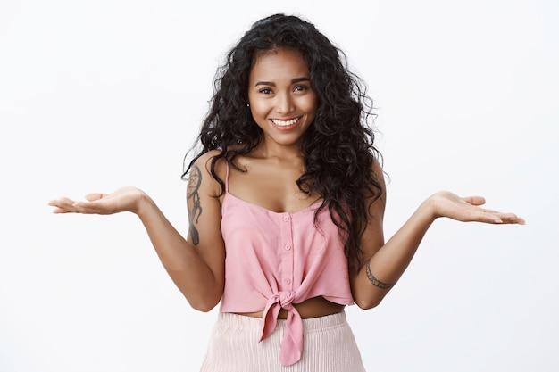 Ontspannen knap meisje met tatoeages, cropped top, schouderophalend en handen onbezorgd zijwaarts spreidend, geen idee hebbend, geen zorgen maken, ongehinderde gevoelens uiten, witte muur
