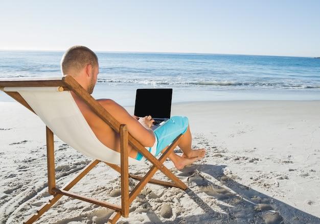 Ontspannen knappe man aan het werk op zijn laptop