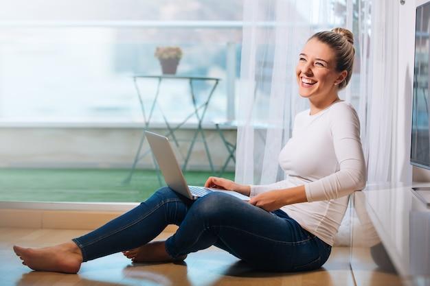 Ontspannen lachende vrouw op blote voeten zittend op de vloer kijkend naar haar laptop
