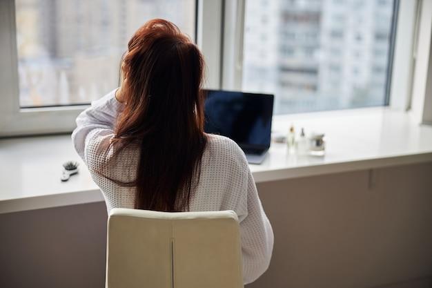 Ontspannen langharige vrouwelijke persoon die naar beautyblog kijkt