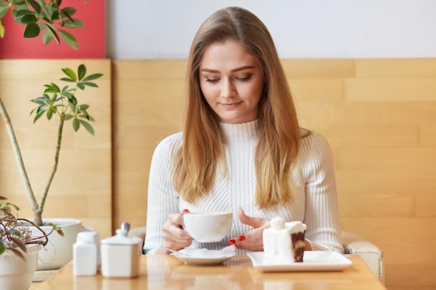 Ontspannen lichtharige vrouw drinkt warme koffie met een heerlijk dessert, zit in een gezellige cafetaria, wacht op vrienden, geniet van vrije tijd tijdens het weekend.